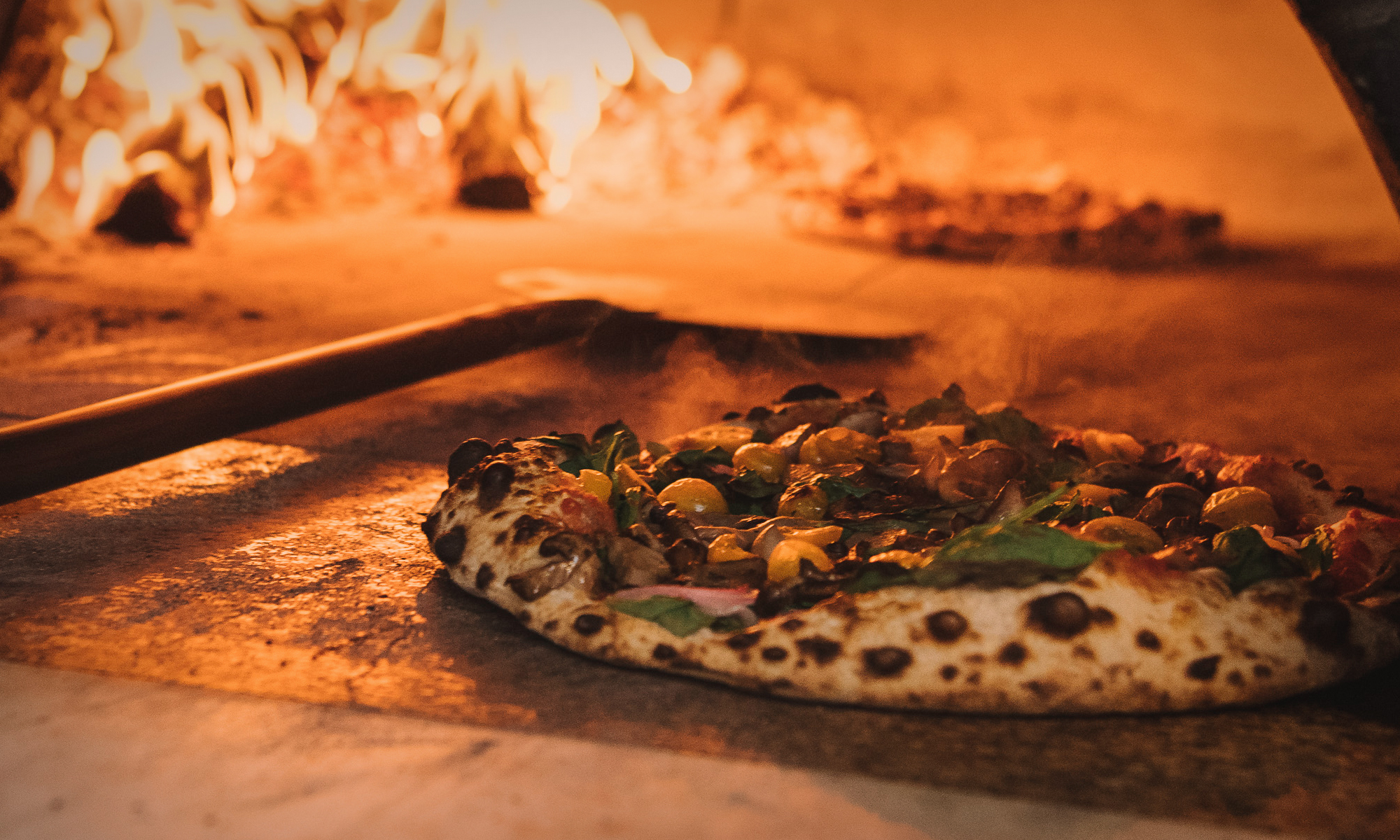 Photo of a pizza baking in our wood-burning oven