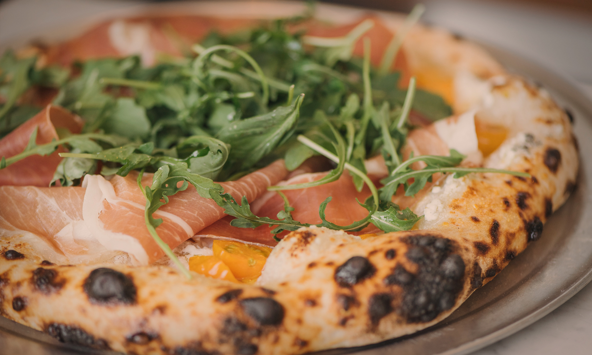 Photo of a prosciutto and arugula pizza