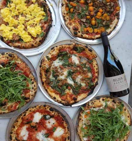Photo of several pizzas and a bottle of red wine