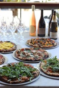 Photo of several pizzas and bottles of wine
