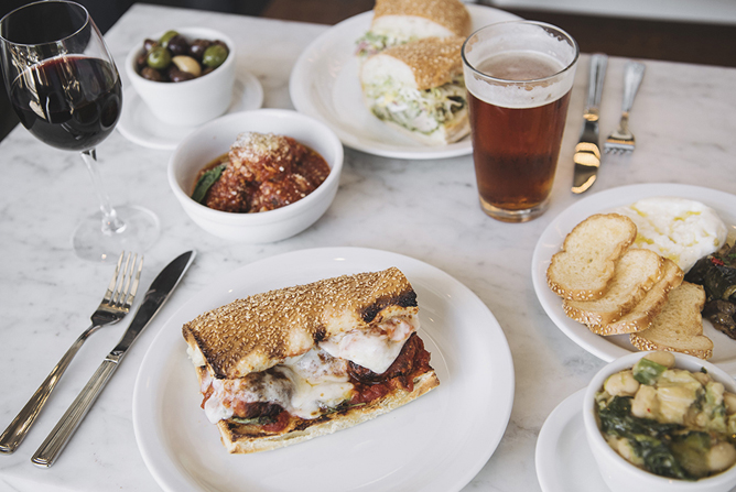 A Live Fire meal for two: sandwiches, a meatball appetizer, a salad, beer, and wine