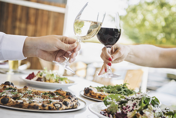 Couple toasting with wine over pizza and salad