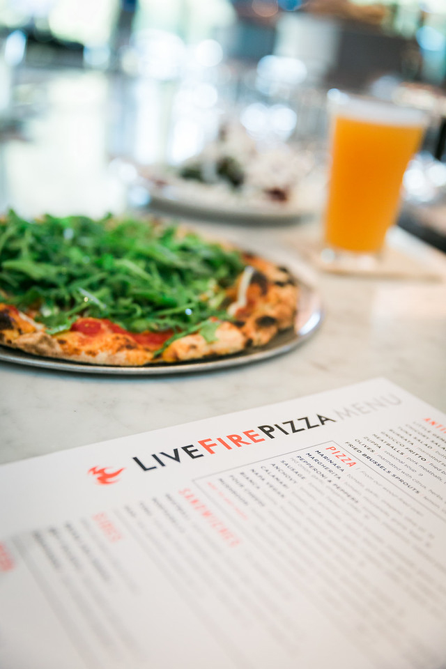 Photo of a pizza beside the Live Fire Pizza menu