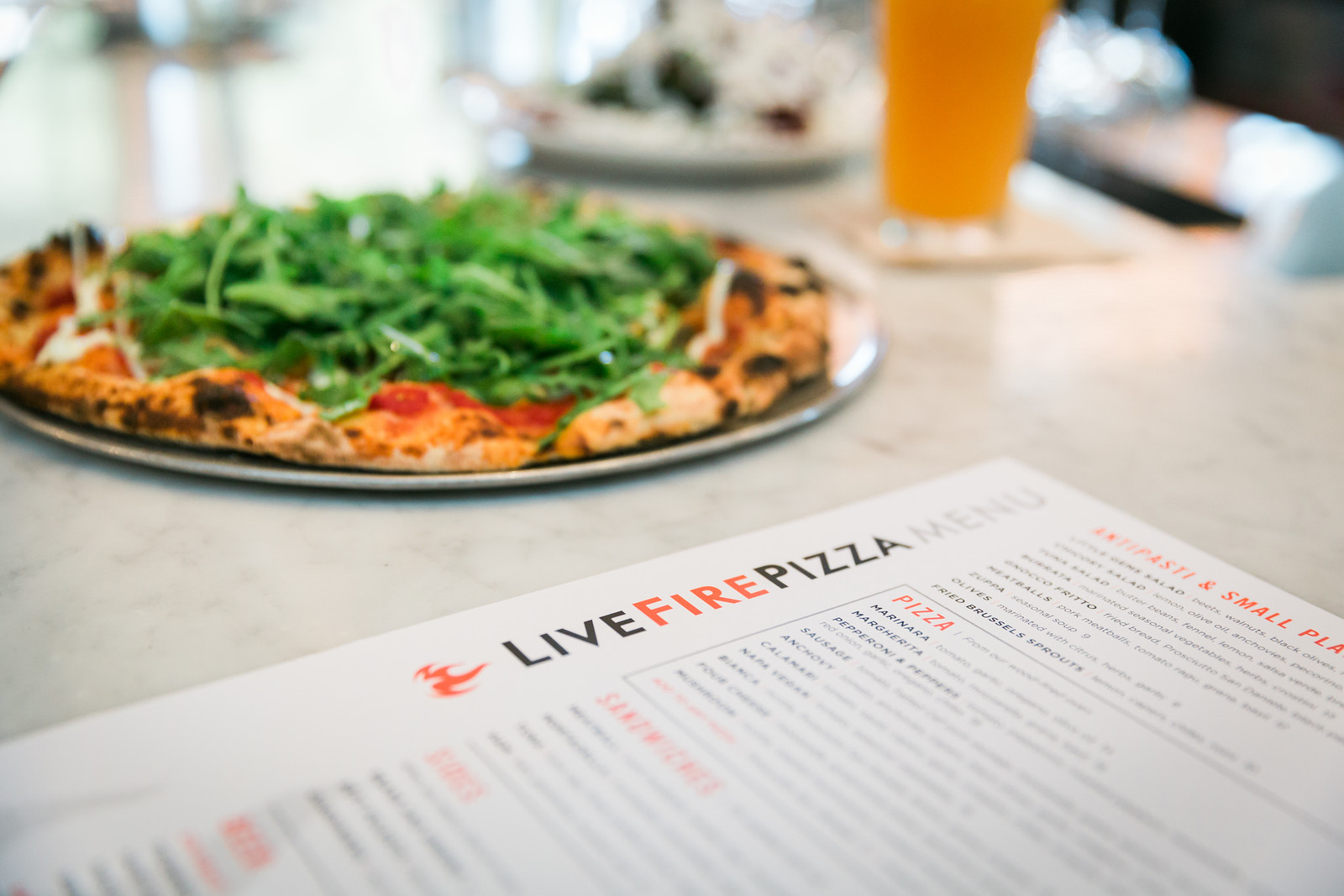 Photo of pizza next to the Live Fire Pizza menu